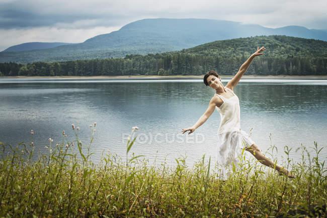 Женщина, танцы на открытом воздухе вдоль берега озера вблизи штата Woodstock, Нью-Йорк, США — стоковое фото