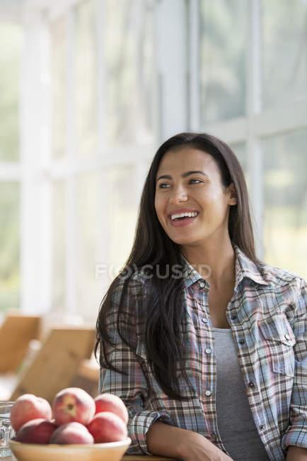 Счастливая молодая женщина сидит за столом с миской персиков . — стоковое фото