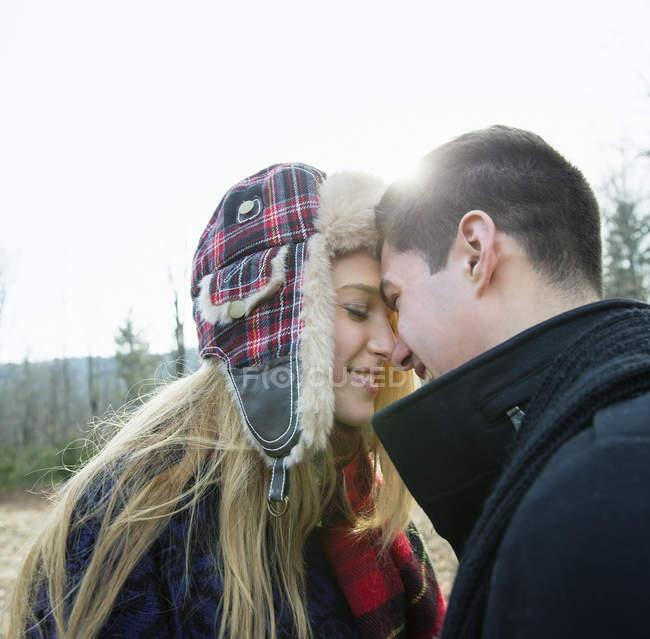 Jeune couple debout face à face et embrassant dans forêt hivernale. — Photo de stock