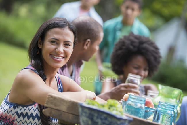 Jeune femme souriant à la caméra avec des amis à la table de pique-nique dans le jardin de campagne . — Photo de stock