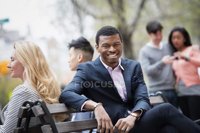 Взрослых, опираясь на город скамейке с людьми, проверка смартфон в фоновом режиме. — стоковое фото