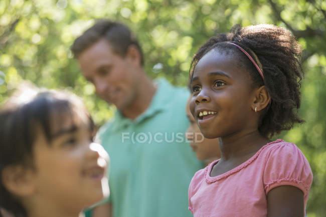 Grupo de niños y hombre adulto medio de pie a la sombra de los árboles en el bosque . - foto de stock