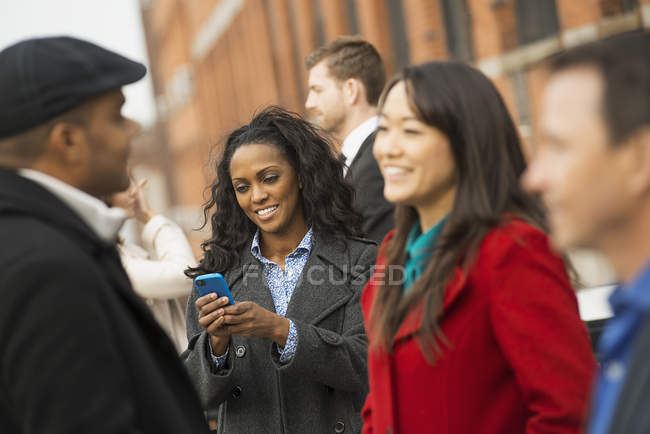 Woman standing on street with mobile phone and group of people in New York, USA — Stock Photo