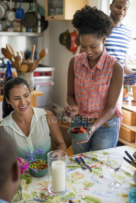 Group of friends laughing while dinner in country kitchen interior. — Stock Photo