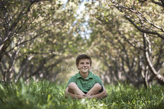 Мальчик, сидящий со скрещенными ногами в лесном туннеле из ветвей деревьев . — стоковое фото