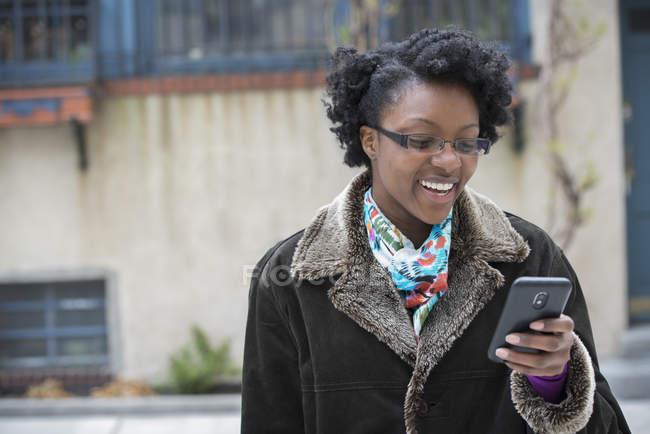 Frau mit Brille lächelt und nutzt Smartphone auf der Straße. — Stockfoto