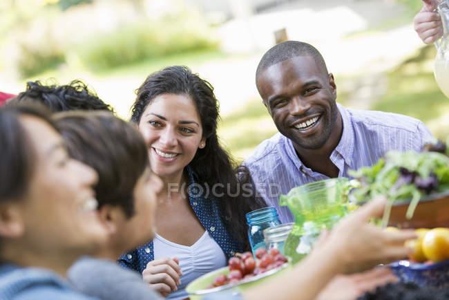 Друзі, сидячи на відкритому повітрі таблиці в саду з фруктів і овочів. — стокове фото