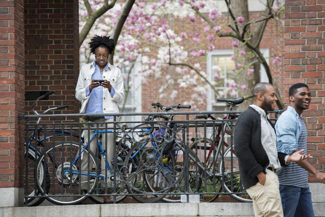 Femme textos sur rack avec des vélos verrouillés avec deux hommes marchant sur la rue . — Photo de stock