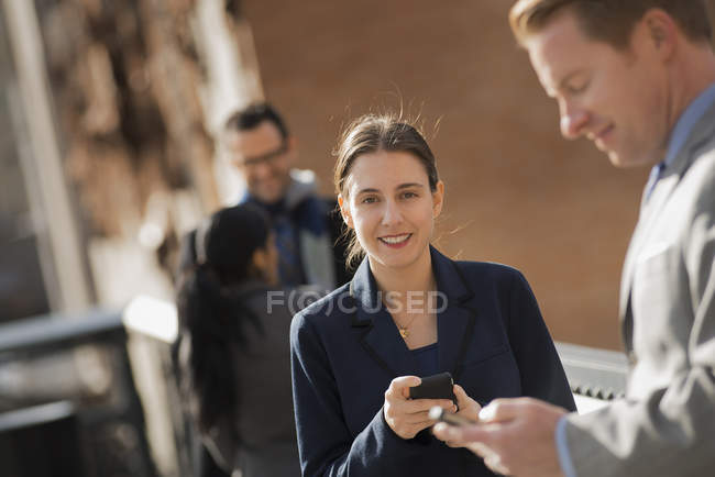 Woman standing on street with mobile phone and group of people  in New York, USA. — Stock Photo
