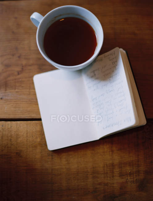 Cup of coffee and handwritten journal on wooden table. — Stock Photo