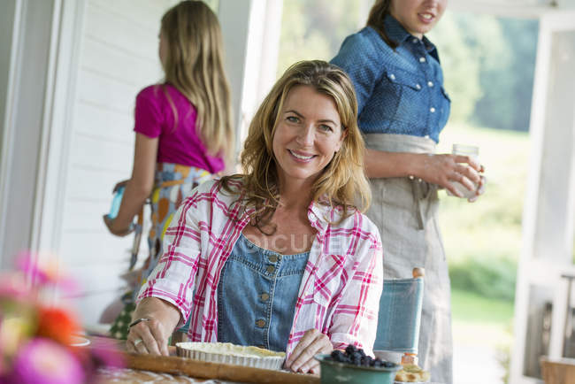 Mid adult woman cooking at outdoor table with family on farmhouse terrace. — Stock Photo