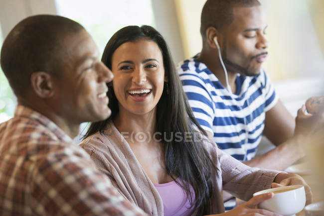 Young couple talking in coffee shop with man wearing earphones in background. — Stock Photo