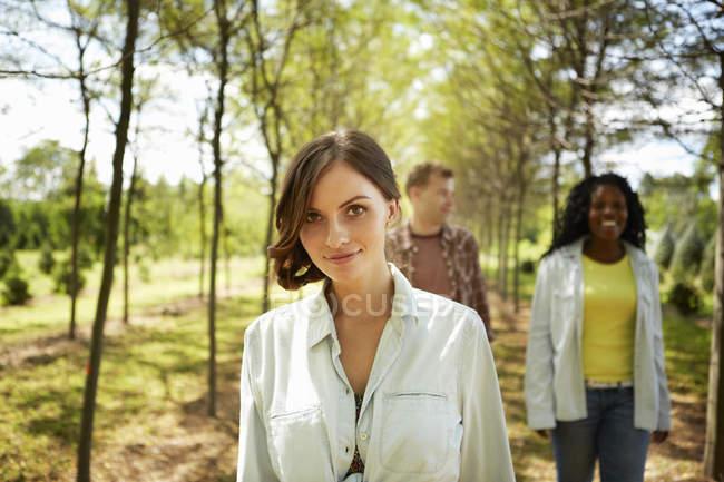 Молоді жінки і чоловік ходіння по країна шлях влітку. — стокове фото