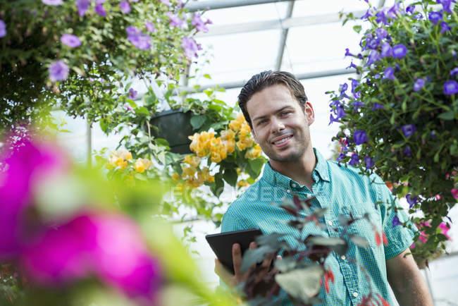 Jovem, segurando o tablet digital em estufa de flor de viveiro — Fotografia de Stock