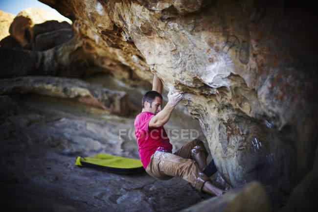 Uomo che si arrampica sullo strapiombo della parete rocciosa con attrezzatura minima . — Foto stock