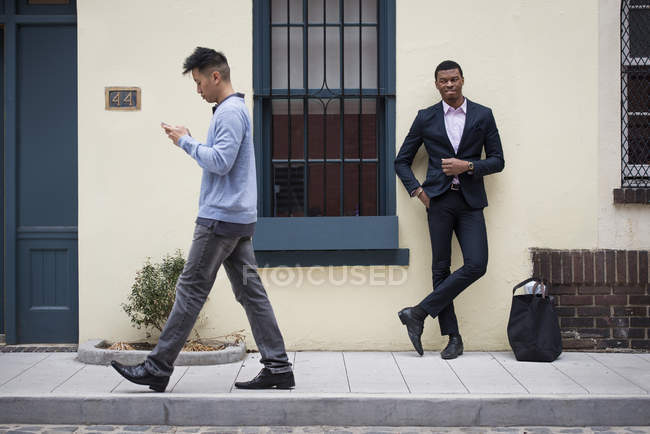 Man in full suit leaning against wall with Asian man walking past and checking phone. — Stock Photo