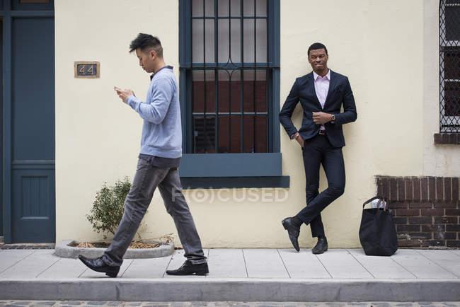 Homem de terno completo, inclinando-se contra a parede com homem asiático passando e verificando o telefone — Fotografia de Stock