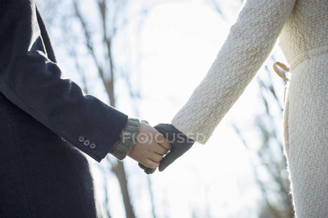 Abgeschnittene Ansicht von Paar Händchen haltend im Wald im Winter. — Stockfoto