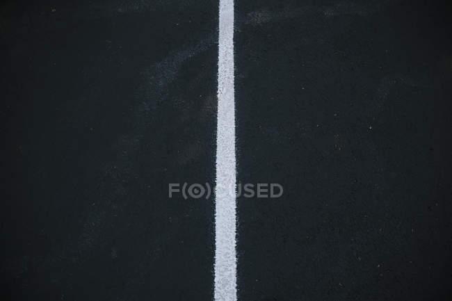 White center line on black asphalt surface. — Stock Photo