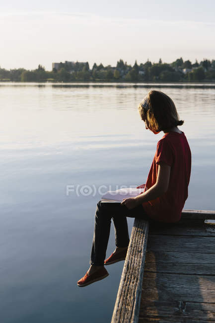Pre-adolescent girl sitting on wooden dock and reading book. — Stock Photo
