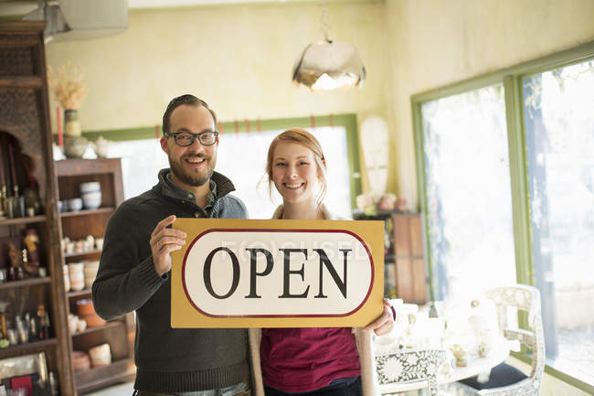 Apre di coppia in piedi nel negozio di antiquariato e che tiene grande segno. — Foto stock