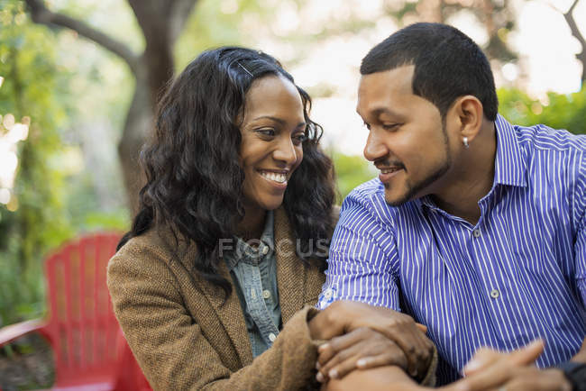 Casal adulto médio com braços ligados sentado lado a lado no parque da cidade . — Fotografia de Stock