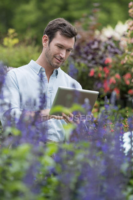 Mid adult man using digital tablet at organic plant nursery. — Stock Photo