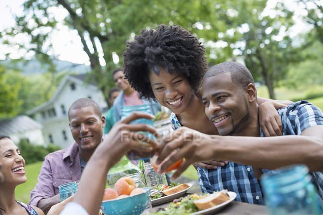 Jóvenes amigos animando con bebidas en la mesa de picnic en el jardín del campo . - foto de stock