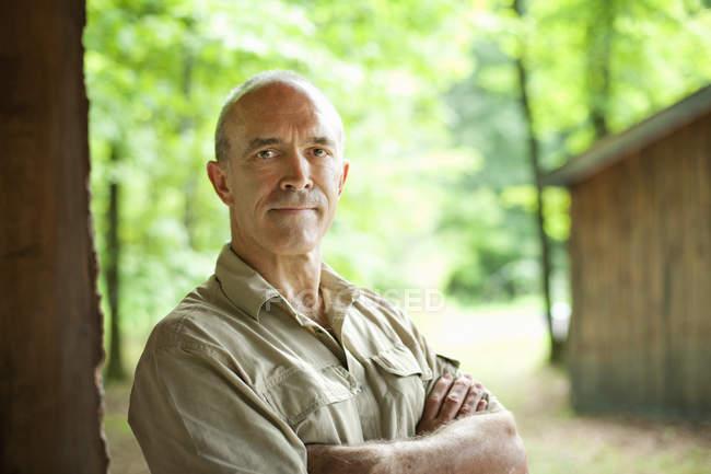 Homme mûr debout avec les bras croisés devant une cabane en bois dans la campagne — Photo de stock