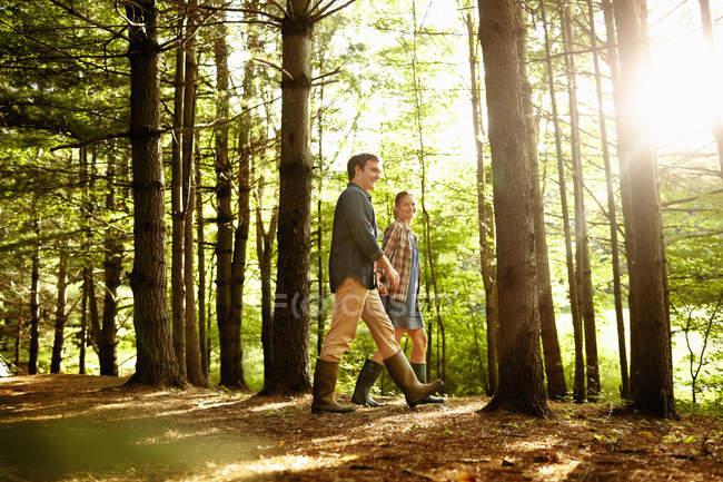 Средний взрослый пара, ходить в Солнечный лес, вид сбоку. — стоковое фото