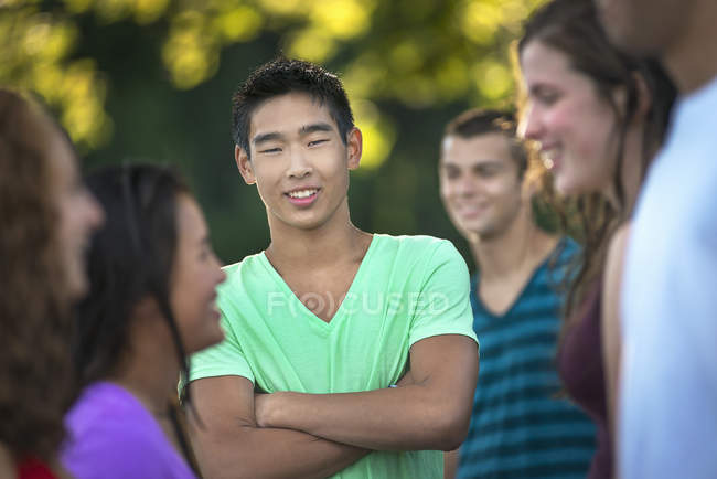 Teenage boy standing with arms crossed in group of young laughing friends outdoors. — Stock Photo