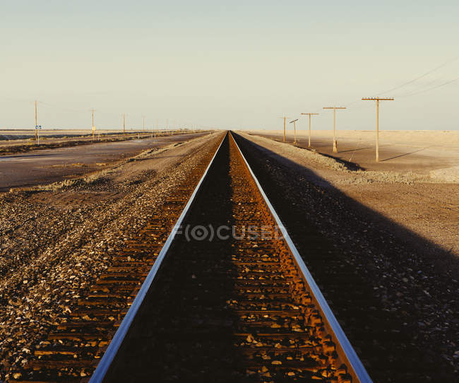 Railroad tracks extending across flat Utah desert landscape at dusk, USA. — Stock Photo