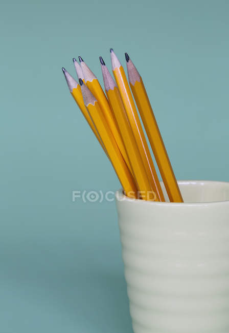 Crayons aiguisés en tasse sur fond bleu . — Photo de stock