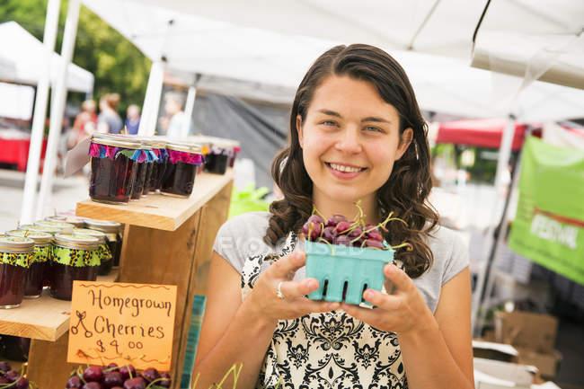 Jeune femme tenant punnet de cerises au stand du marché fermier . — Photo de stock