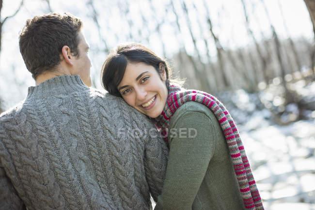 Молодая пара, обниматься на улице в зимний лес. — стоковое фото