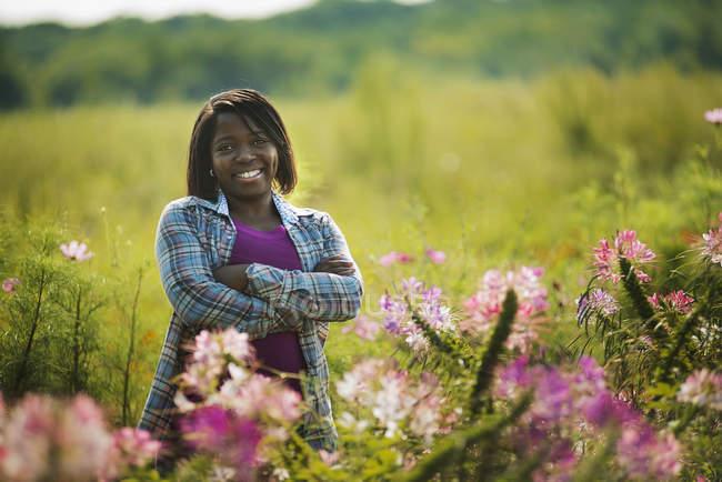 Женщина, стоящая в луг с сложив на ферме органических цветок — стоковое фото