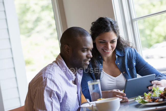 Couple sitting at cafe and looking at digital tablet. — Stock Photo