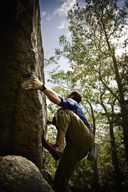 Uomo che si arrampica ripide scogliere nei boschi vicino a Essex, Massachusetts. — Foto stock