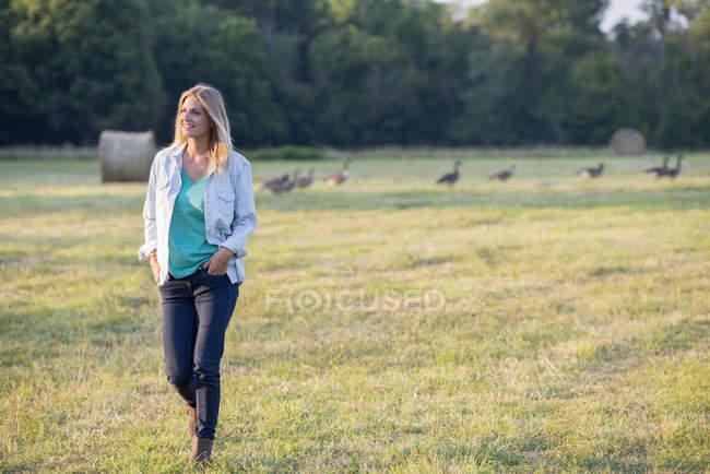 Frau läuft mit Gänseschar über Feld. — Stockfoto