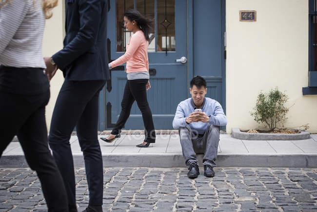 Homme assis sur le trottoir et la vérification téléphonique avec les passants sur la rue. — Photo de stock