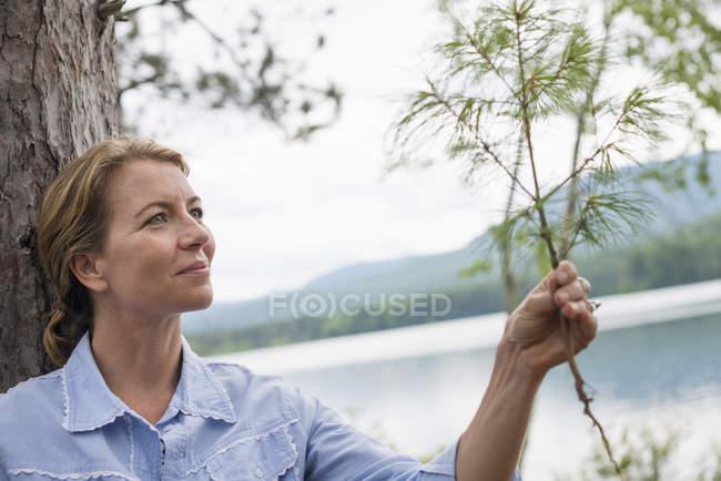 Зрелая женщина держит прутик на берегу озера в сельской местности . — стоковое фото
