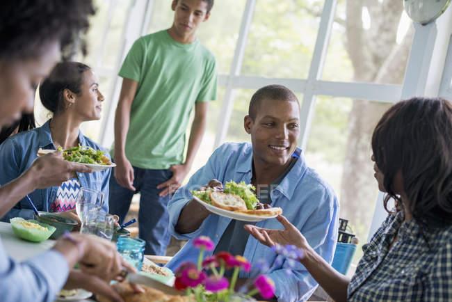 Группа мужчин и женщин ужинают в интерьере загородного дома . — стоковое фото