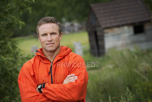 Mid adult man with arms folded in bright orange jacket posing in countryside. — Stock Photo