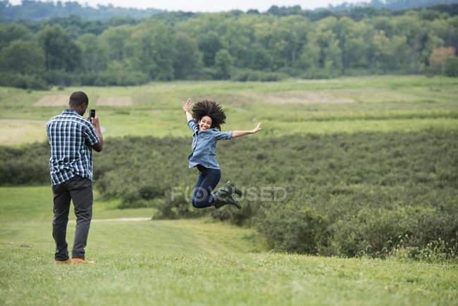 Картина принимая человек прыгает с оружием протянутой в сельской местности женщины. — стоковое фото