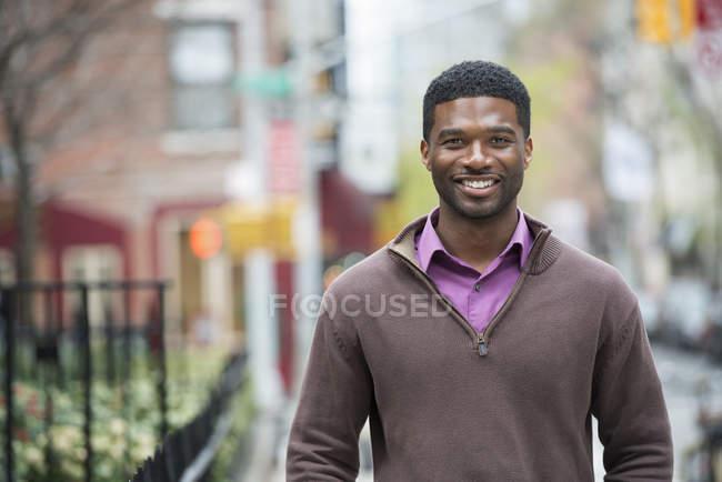 Hombre joven con camisa morada y jersey suéter sonriendo en la calle . - foto de stock