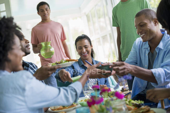 Group of women and men sharing dinner in country house interior. — Stock Photo