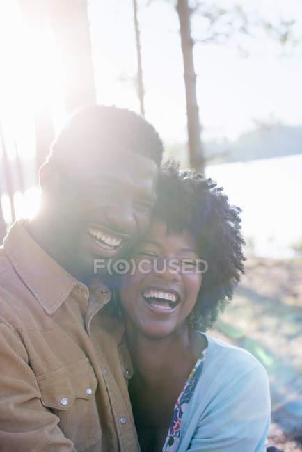 Pareja feliz abrazándose y riendo en bosques soleados . - foto de stock