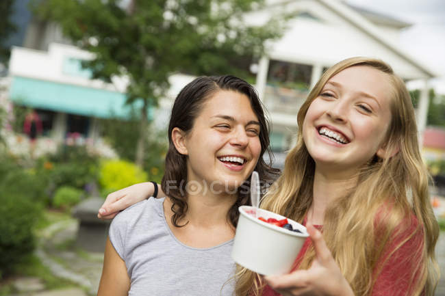 Teen girls hugging, laughing and holding bowl of ice cream — Stock Photo