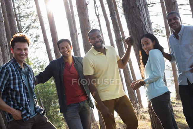 Groupe d'amis réunis à l'ombre des pins au bord du lac en été . — Photo de stock