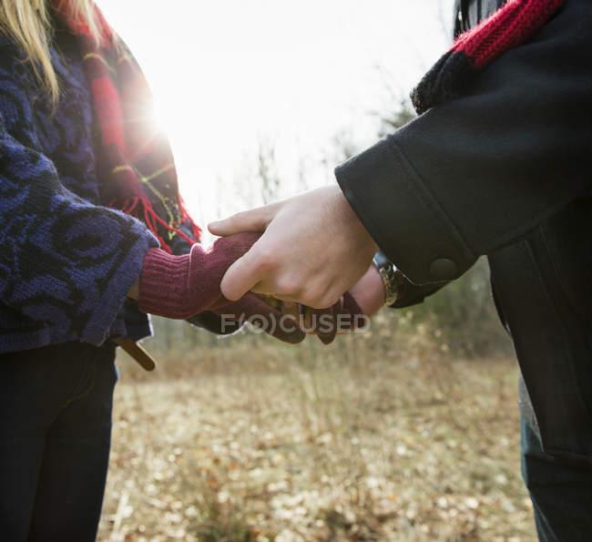 Обрезанное зрения пара в зимние пальто, взявшись за руки в зимний лес — стоковое фото